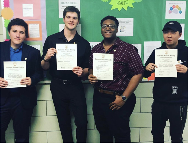 Photo of four students holding certificates