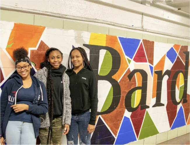 Three smiling students standing in front of a Bard mural